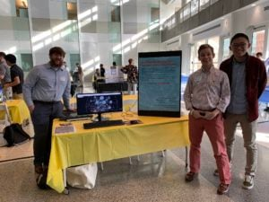 Three students stand around their table on the expo floor. The table includes flyers, a monitor displaying an application, and a display poster with a link to a live version of the app.