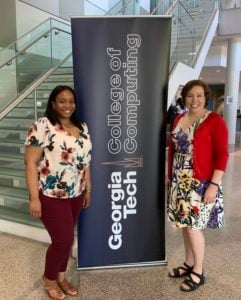 Alyshia Jackson and Amanda Girard stand by the Georgia Tech College of Computing banner at the Spring 2019 Expo