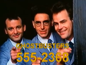 "Image of Bill Murray, Harold Ramis, and Dan Akroyd from the 1984 film Ghostbusters. All three point at the viewer as part of an in-film commercial; the text and fictitious phone number ""Ghostbusters 555-2368"" scroll across the bottom of the screen."